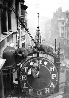 Workmen dismantling the clock outside the #DailyTelegraph for the building's remodel c.1930. #London