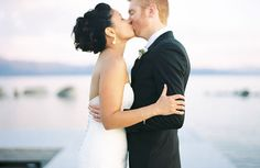 The newlyweds share a kiss in front of glittering Lake Tahoe. Emily Scannell Photography.