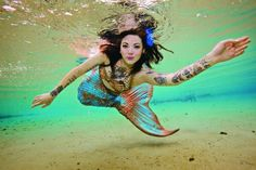 Tattooed mermaid swimming above golden sands.