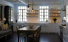 table in middle of kitchen, pendants, black windows