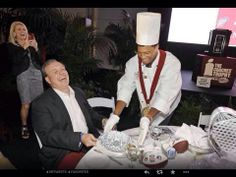 """Coach Jimbo Fisher being """"served"""" by QB Jameis Winston. Coach Fisher's wife is taking a picture."""