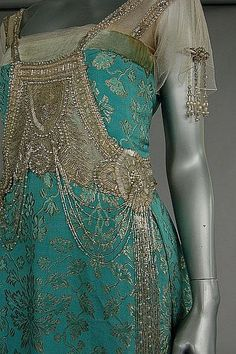 A turquoise and gold brocaded satin evening gown, circa 1917, un-labelled, the bodice adorned with tasselled panel of silver bugle beads, tulle sleeves, above draped skirt with wide inner petersham waistband. Detail