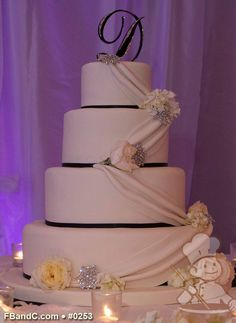 "Design W 0253 | Fondant Wedding Cake | 16""+12""+9""+6"" | Serves 190 | Fondant drapes, black fondant band on base, fresh flowers, broaches  | Custom Quote"