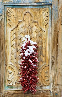 A chile ristra covered with a dusting of snow makes a colorful compositon against a caved wooden door in Santa Fe, New Mexico.