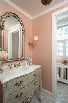 "Love the ornate carved wood vanity in antiqued cream plus the white ""marble"" lavatory and antique silver-framed mirror in this powder room.  Other colors besides pink would work as well on the walls."
