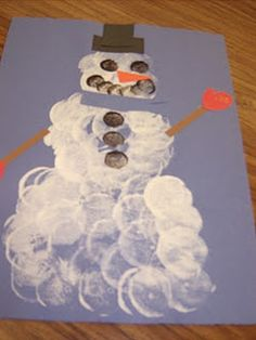 Marshmallow Art Snowman  The marshmallow snowman's body is made by dipping a large marshmallow into white paint.  The buttons and face are made by dipping a small marshmallow into black paint.  The accessories are made out of paper.
