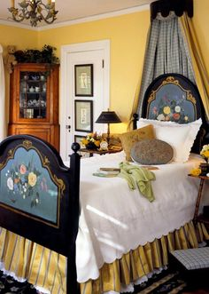 a guest bedroom in a dream cottage--custom-painted bed, tole lamps, antique botanicals hung on closet door