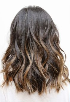 Wavy brown hair with warm highlights