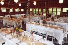 An inside shot of the rustic barn for the wedding reception and dinner at the West Mountain Inn venue in Arlington, VT.  With twinkle lights, burlap table runners, wildflowers and white tablecloths and chairs, this venue can provide a rustic AND chic spot to tie the knot!  #westmountaininn #rusticwedding #barn #vt