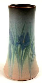 Rookwood Pottery vellum glaze vase adorned with a blue iris against a matt glaze background that shades from dark blue to light blue and finally into peach. Decorated by Caroline Steinle, 1913
