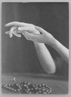 Photo by E.O. Hoppe - Close-up of a woman's graceful hands with ring and necklace in foreground, 1925.