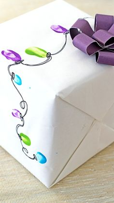 Christmas Wrapping ~ a simple pen and craft paints turn tiny fingerprints into a single strand of Christmas lights,...  a fabulous way to make a gift even more special