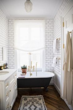 black with hardwood floors, subway tile with dark grout, carrera marble vanity top
