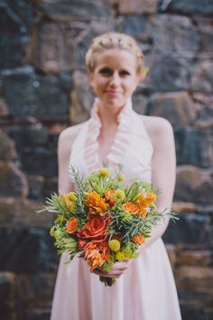 orange and green bouquet with billy buttons, photo by Mel Nocks Photography http://ruffledblog.com/whimsical-greenville-wedding #weddingbouquet #flowers