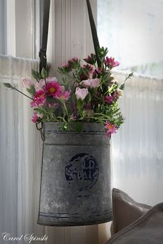 I love flowers hanging in galvanized tins!