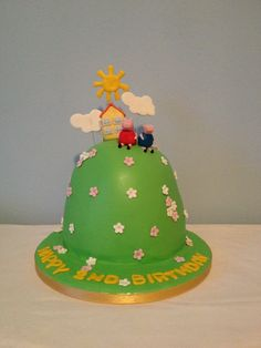 """Peppa Pig cake - A Peppa Pig cake for a little girl's 2nd birthday.    Wilton Ball pan, 2x 7"""" sponges carved down.    Clouds and sun on wires. Tiny Pig house and Peppa and George"""