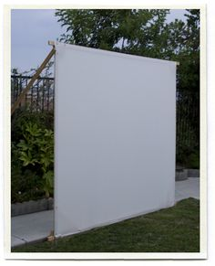 DIY movie theater -the screen is made out of an old queen sized flat sheet, stretched across some spare wood...perfect for outdoors or the basement!
