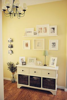 entryway~love the photo layout and shelf..nice yellow wall