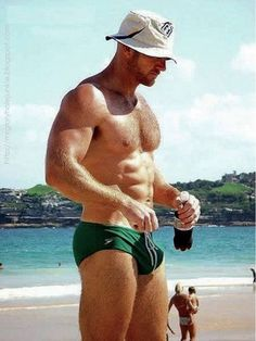 Ginger muscle packed into the real deal - a green men's Speedo with strings carelessly hanging out.