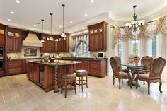 U-shaped kitchen in upscale home with wood cabinets, tile floor opening up to small dining nook