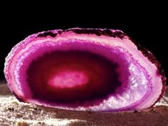 A pink chalcedony shows off its beauty. Chalcedonies include many types of cryptocrystalline quartz gems and feature a number of different colors. Geologists can tell a chalcedony from the arrangement and structure of its crystals.