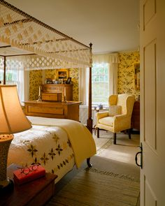 A netted canopy on the four-poster bed and revival wallpaper show Colonial Revival sentiment in the master bedroom.