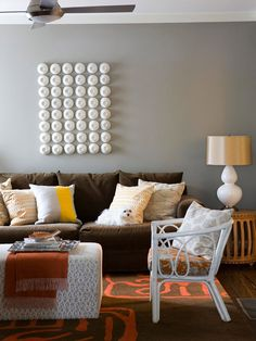 love the brown couch as a neutral and the white wicker furniture.  Add some light blue or green throw pillows.