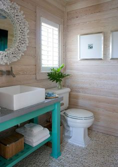 white washed wooden walls, pebbled floor, coral mirror and a splash of turquoise do a beachy bathroom make via House of Turquoise