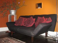 """Here are two photos for your used stuff blog if they suit your needs...One is a loveseat I found on the sidewalk the other day.  It was missing a leg so I went to the Rebuilding Center and bought a railing spindle, went to the Tool Library and borrowed tools and created a leg.  Looks and works great!  In the background of the photo are some old chimney inserts I found and now use as a pedestal. The metal barrel I found on a sidewalk and the magnolia blossoms are from a street tree pruning."""
