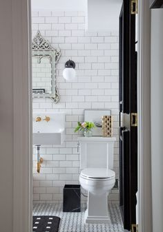 Beautiful bathroom with classic subway tile - love the mirror and brass fixtures.  Part of this gorgeous home tour at eclecticallyvintage.com