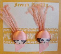 Exquisite and rare French Flapper Face buttons adorned with Ostrich feathers on original card. c. 1920 feather origin, powder puff, face button, flapper face, flapper button, 1920s french, french flapper, origin card, ostrich feather
