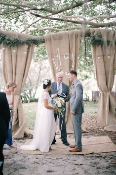 This ceremony backdrop is made of burlap, hung in several places over a low tree branch and tied lightly in the middle.