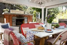 Patio outfitted with outdoor fireplace and a custom canvas structure with roll-down shades to block wind. #countryliving #porch