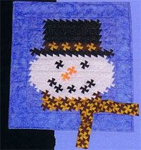 """Snowman Twist Pattern by A Very Special Collection at KayeWood.com. This pattern includes instructions for three sizes. The small size uses the Itty Bitty Primitive Pinwheel Tool and is 20"""" x 22"""". The medium size uses the Primitive Pinwheel Tool and the large size uses the Lil' Twister Ruler. Both the small and medium sizes have a scarf that hangs and can be positioned to look like it's blowing in the wind. The large scarf does not hang it goes around the neck of the snowman.  $9.00"""