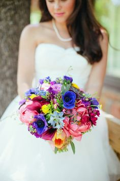 Love all the bright colors in this bouquet against the beautiful white dress.. lovely.