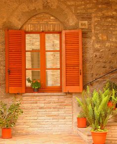 Love the neutrality of the tan brick with the punchy orange shutters and flowers.