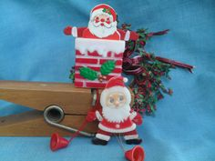Vintage Santa Claus Hard Plastic Christmas Pins Pop Up Motion. A Santa Claus that pops out of the chimney when you pull the bell on the bottom. And, a Santa that does jumping jacks when you pull his bell. 1960s – 1970s.
