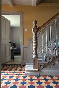 hallway - foyer - grey painted stairs with quatrefoil detail on side - grey paneling - blue, muted red & muted yellow checkerboard tile floor - photo by David Merewether