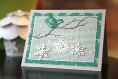 handmade winter card ... die cuts and patterned paper .. three punched snowflakes hanging on a die cut branch ... bird in on the branch and little snowflackes sprewn about ... delightful card with dimension and a bit of glittery sparkle ...