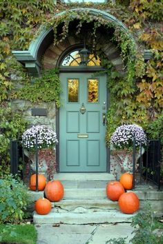 Enjoy the simplicity of the orange pumpkins combined with the lavender mums and blue-green front door.