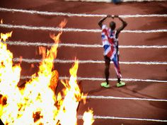 Mo Farah is seen through the heat of the Olympic flames as he poses with the union flag after winning gold in the men's 10,000m final by Dan Chung.