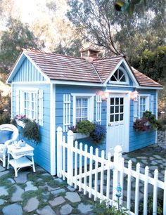 Blue Tiny House With White Fence