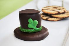 What's luckier than a leprechaun's hat? A leprechaun hat made of chocolate and marshmallow with a great cookie crunch! An easy treat for St. Patrick's Day! Delicious as they are cute, Fudge Stripe Cookie base  topped with a marshmallow and  and then coated in chocolate to create one delicious little s'more hat!   Easy enough for your little leprechauns to help make too.