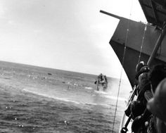 Crew of USS Yorktown watch as Destroyer USS Hammann sinks stern high after being stuck by torpedoes from a Japanese submarine during the Battle of Midway, 4-7 June 1942.