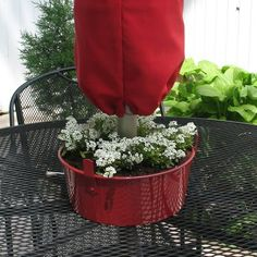 Plant flowers in a painted angel food cake pan and slide the umbrella through it.