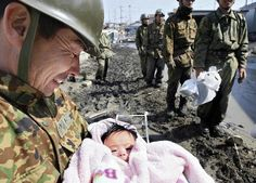 4-month-old baby girl in a pink bear suit is miraculously rescued from the rubble by soldiers after four days missing following the Japanese tsunami