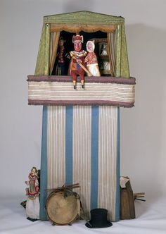 The Baby's Cry; Gus Wood's Up-to-date Punch and Judy  Object:Puppet booth  Place of origin:England, Great Britain (made) Czech Republic (made)  Date:ca. 1912 (made) 1930 - 1939 (printed)  Artist/Maker:Gus Wood (Some figures were carved by Gus Wood, others were acquired at the time he started as a puppeteer. In, makers)   Acme Whistles (Whistle attached to puppet., manufacturers)   Thomas Townend & Co. (manufacturers)    Materials and Techniques:  Carved wood and other material