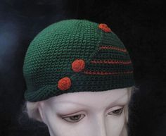 Stylish 1920s crocheted cloche hat with a whimsical Art Deco design featuring a turned-up brim and a triangular flap with applied spiral disks in two shades of green and orange.