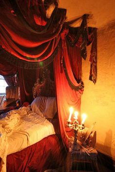 love the Dracula like feeling- Gothic- from the colors and fabric swags.  Gives me ideas for decorations.