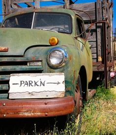 "The ""park'n"" sign for this country wedding stood on the bumper of an old antique farm truck."